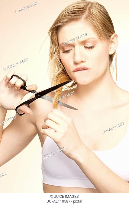 Young woman cutting long hair with scissors