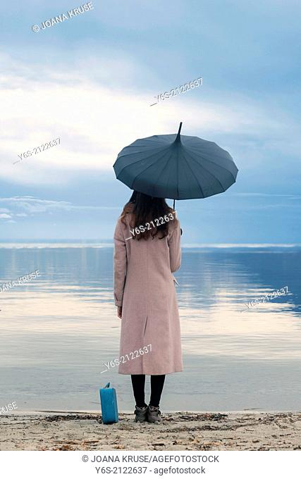 a woman in a pink coat with umbrella and suitcase is standing at a lake