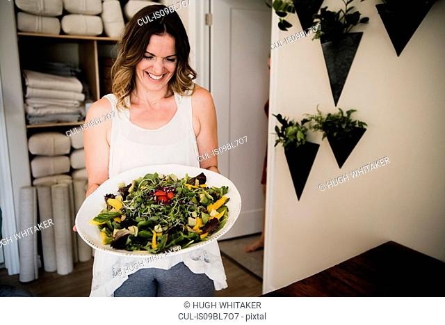 Woman serving large dish of salad at retreat