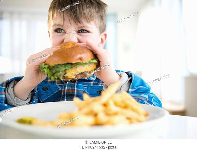 Portrait of boy (4-5) eating hamburger