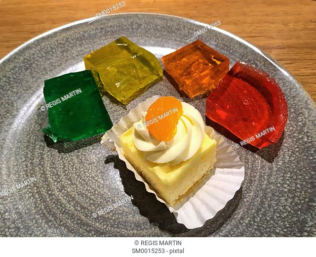 Mini cake and four pieces of jelly on a plate