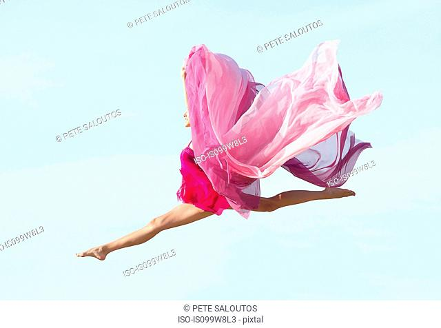 Ballerina jumping with fabric side view