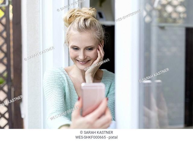 Blond woman sitting at terrace door holding cell phone