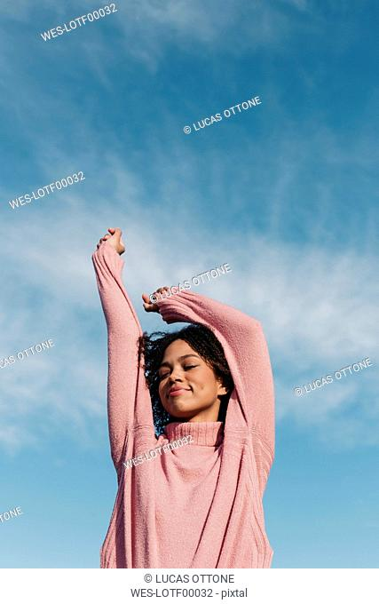 Portrait of smiling young woman wearing pink pullover against sky
