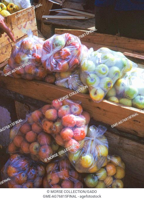View of large clear plastic bags filled with red and yellow apples for sale in the Golan Heights, near the Banias, Israel, November, 1967