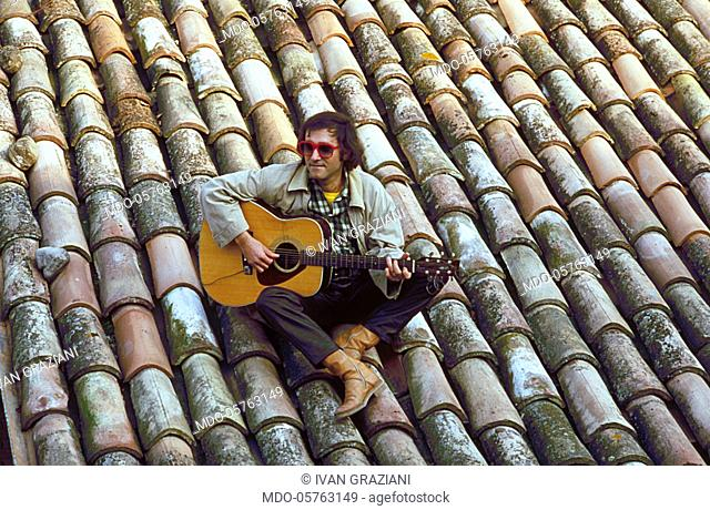 Italian singer-songwriter Ivan Graziani sitting on a roof and playing the guitar. 1979