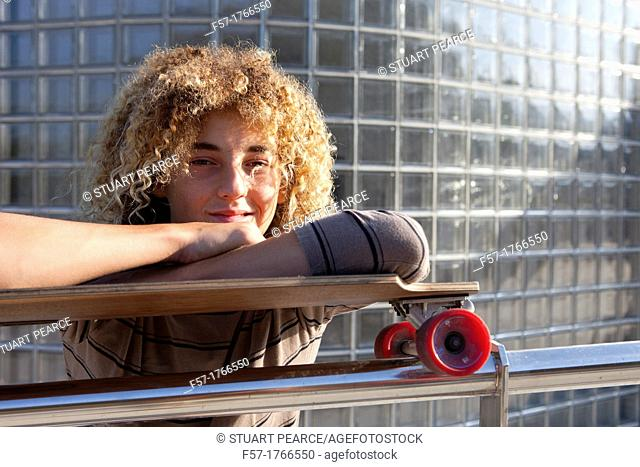 Teenage boy leaning on his skateboard
