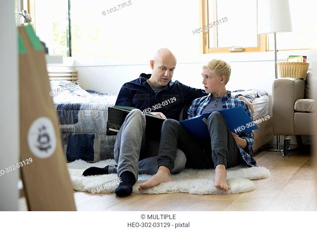 Father helping son with homework on bedroom floor