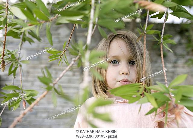 Portrait of little girl between twigs in a garden