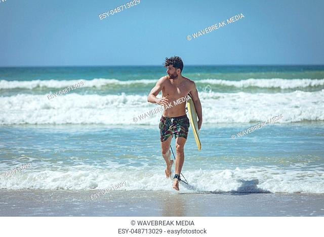 Young male surfer with a surfboard running at beach