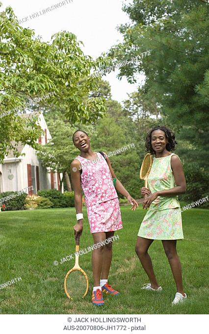 Two mid adult women holding tennis rackets and smiling in a lawn