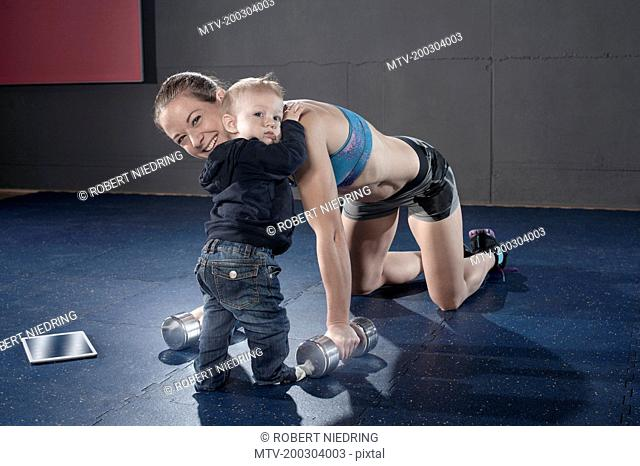 little boy hugging his mother in gym while his mother doing exercise, Bavaria, Germany
