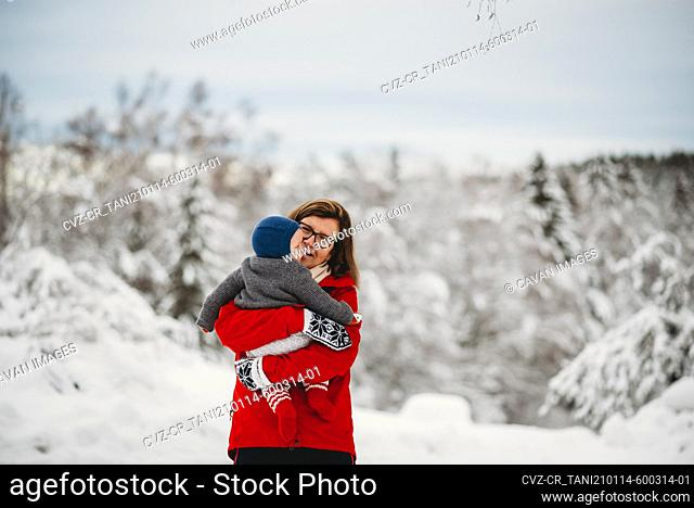 Grandmother holding grandchild baby outside in snow in winter Norway