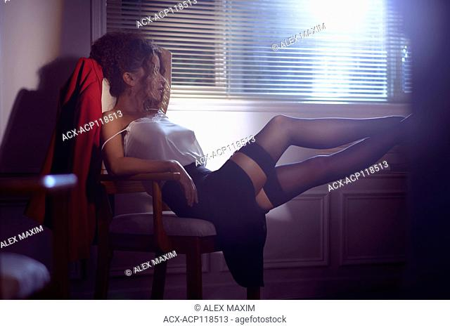 Artistic sensual portrait of a beautiful sexy woman sitting in a chair half undressed with her legs in stockings on a desk in dim night light coming from a...