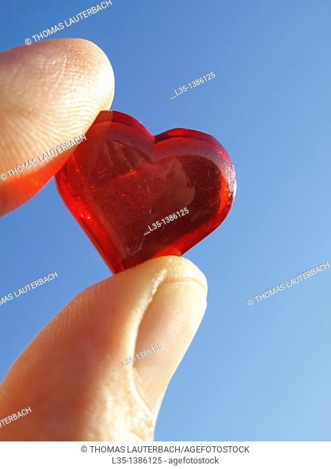Hand holding small glass heart with blue sky