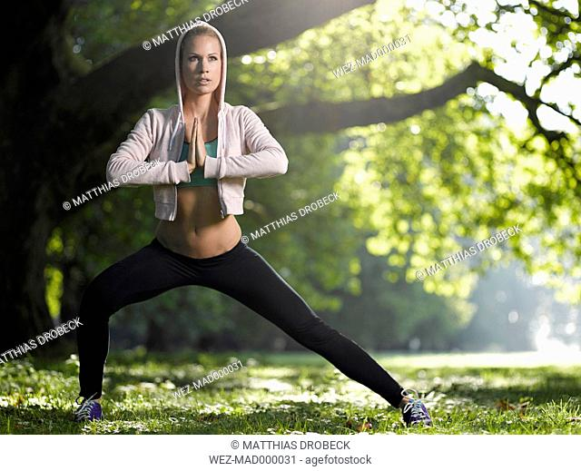 Young woman making stretching exercise on a meadow