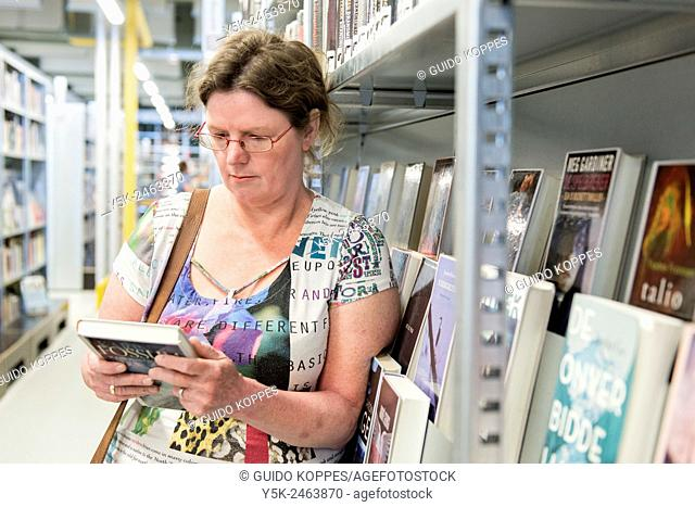 Gouda, Netherlands. Middle aged woman choosing a book to read from the library shelves