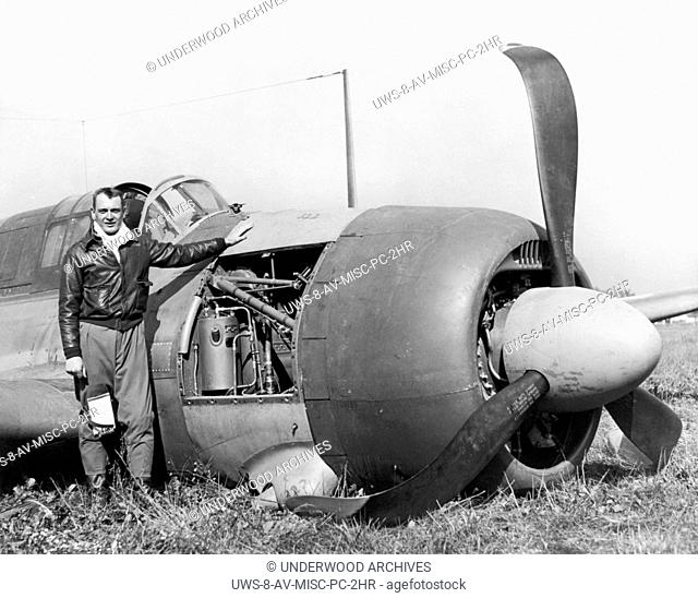 Ohio: September 22, 1943.A pilot standing next to the airplane that was crash landed in a field