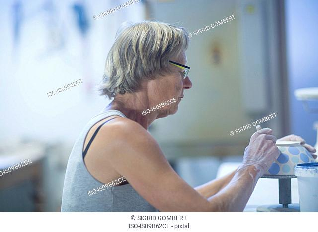 Senior woman in pottery workshop, painting bowl