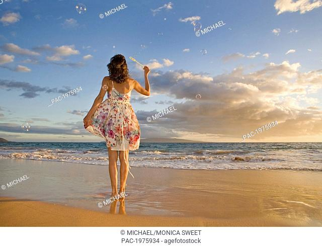 Hawaii, Maui, Woman Standing On The Shore Of Remote Tropical Location Blowing Bubbles