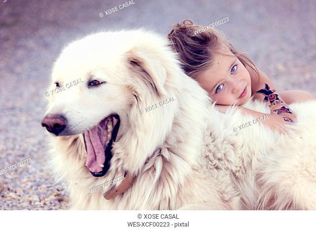 Portrait of little girl cuddling yawning white dog