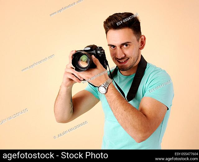 Young professional photographer focusing with his camera and equipment