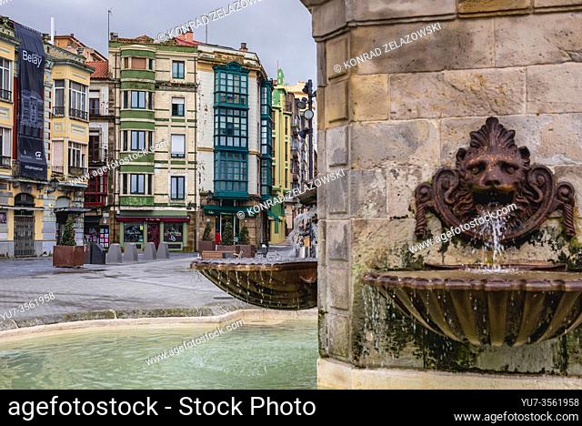 Tenement houses and fountain of Statue of Pelagius, first king of Asturias in Gijon in the autonomous community of Asturias in Spain