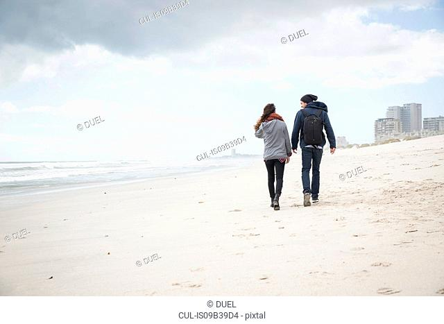 Rear view of young couple strolling on beach, Western Cape, South Africa