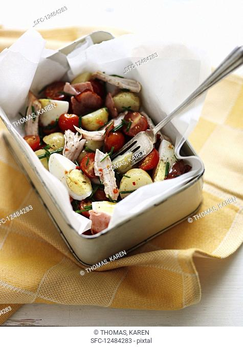 Potato salad with chicken, cherry tomatoes, chives, egg and bacon