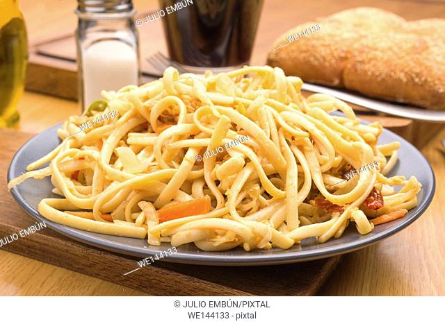 cooked pasta dish with vegetables on wood