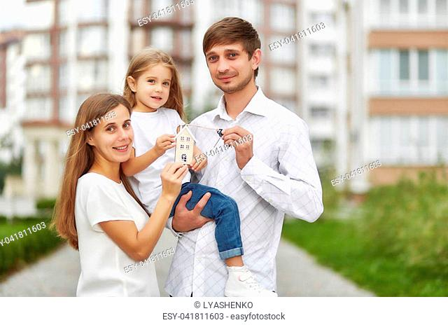 Lovely young family holding keys to their new apartment smiling joyfully posing outdoors. Husband and wife with their child holding keys to new house family...