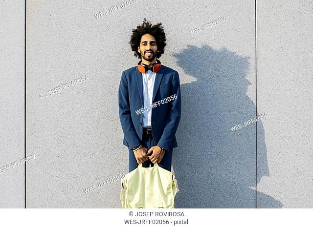 Portrait of smiling young businessman with bag and headphones at a wall