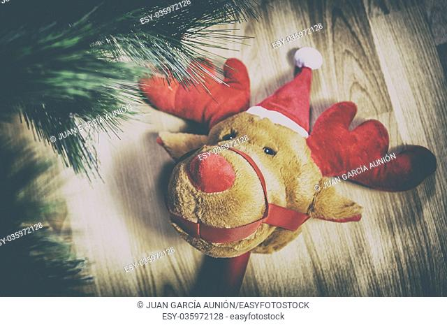 Stick plush reindeer toy over wooden floor close to Christmas Tree at home