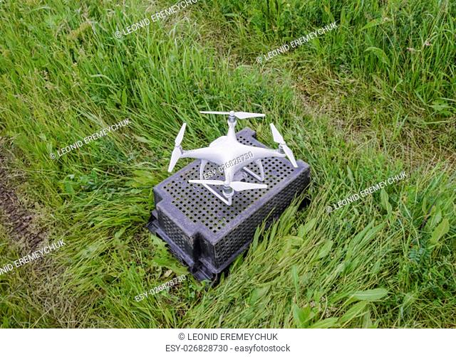 Quadrocopters on a plastic box in the grass. Preparation quadrocopter to fly