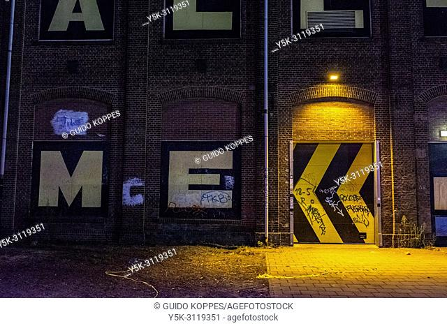 Tilburg, Netherlands. Industrial building door illuminated by a sparse light, early mrning, just before sunrise