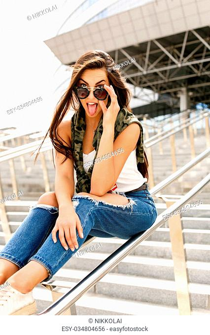 Happy beautiful girl with long healthy hair touch her trendy fashion sunglasses, show her tongue and have fun. Young sexy lady enjoying summer day near business...