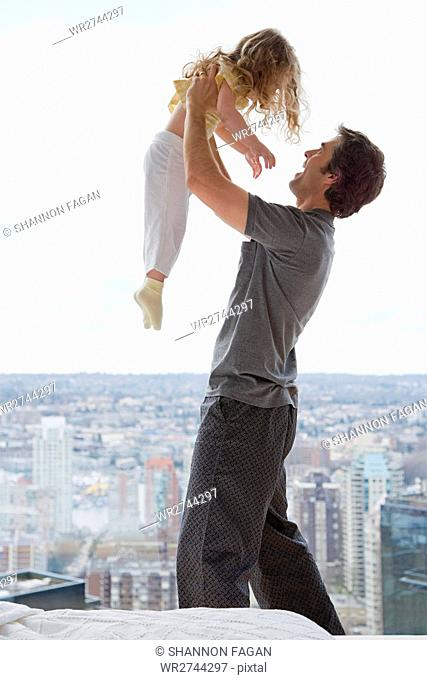 father lifting his daughter
