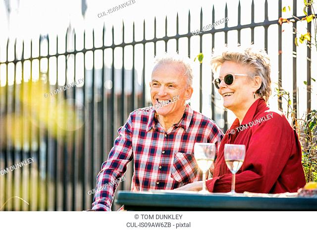 Senior couple on city rooftop garden relaxing with white wine