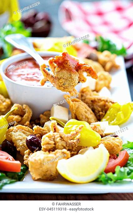 Fried calamari appetizer with olives, pickeld peppers and marinara sauce