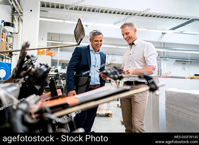 Two happy businessmen looking at folder in a factory