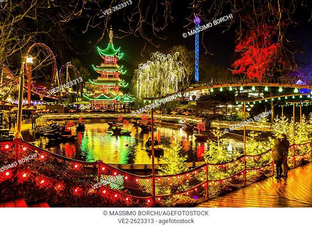 Denmark, Sjelland, Copenhagen . Christmas in Tivoli Gardens, Dragon Boat lake, the Pagoda and the bridge over Tivoli Lake with Christmas decorations