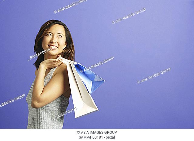 Woman holding shopping bags over shoulder, looking away