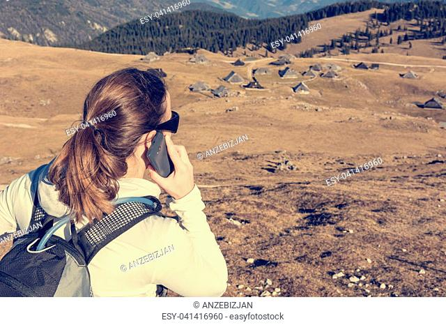 Woman making a phone call in highlands. Velika planina, Slovenia