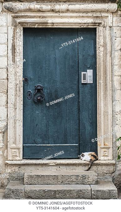 A cat snoozes on a doorstep in the Old Town, Dubrovnik, Croatia, Europe