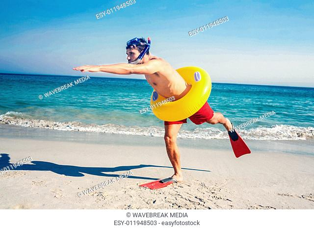 Man wearing flippers and rubber ring at the beach