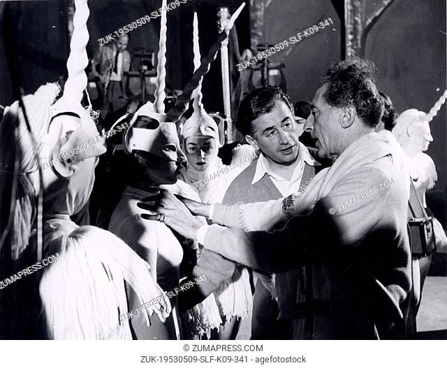 May 09, 1953 - Munich, Germany - JEAN COCTEAU (R) is helping putting the finishing touches to a costume at the premiere of his Ballet 'La Dame a la Licorne'