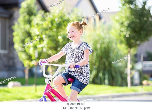 Caucasian girl riding bicycle