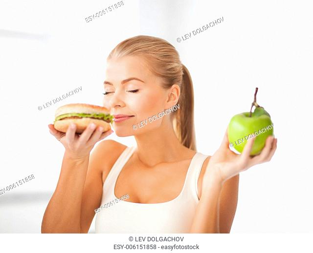 health, diet and food concept - healthy woman smelling hamburger and holding apple