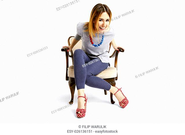 Woman sitting down on a old school chair and laughing