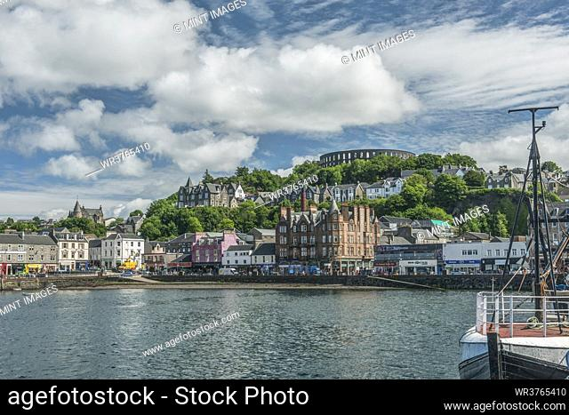 Waterfront town with Coliseum-style monument on hilltop, Mccaig's Tower and Battery